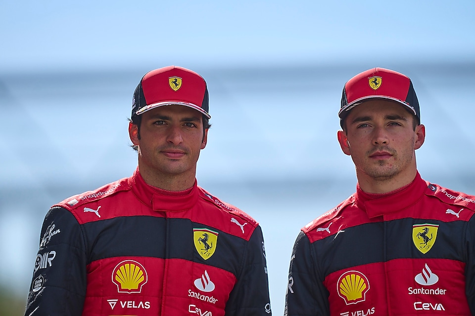 racing team standing in between two red racing cars